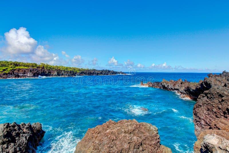 Svart lava vaggar stranden, väg till Hana, Maui arkivfoton