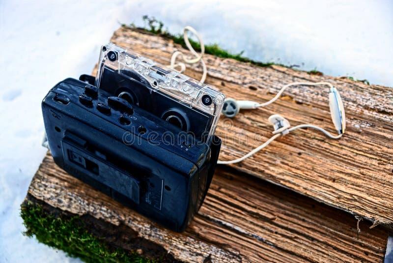 Svart ljudsignal spelare med en kassett på ett trästycke i snön arkivfoto