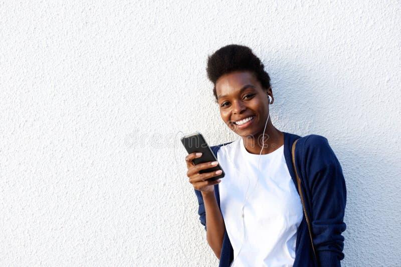 svart lyssnande musik till kvinnabarn arkivfoto