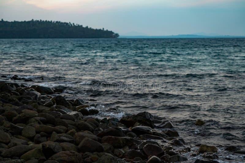 Svart mörk sten på stranden i havet med lite sniglar allt det område Det är twiligttid i asiatet, Thailand royaltyfria foton