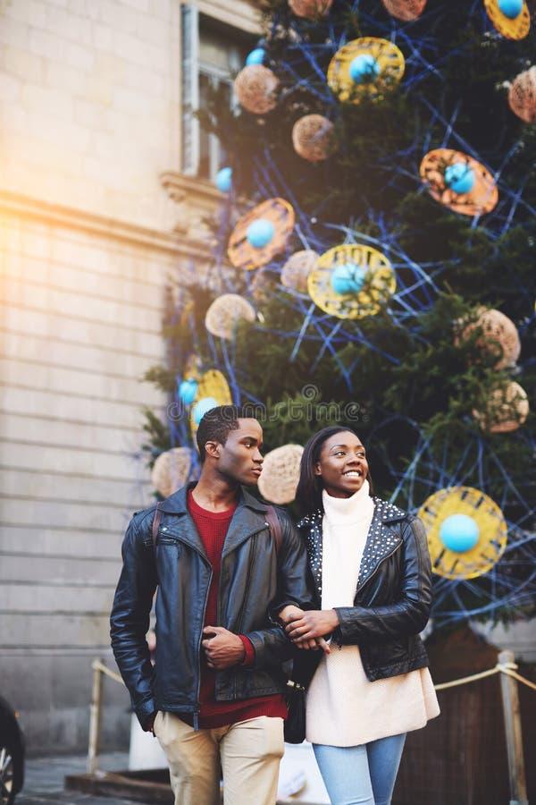 Svart man- och kvinnaturister som går i stads- inställning under deras vinter, tillbringar veckoslutet, härliga par som tycker om fotografering för bildbyråer
