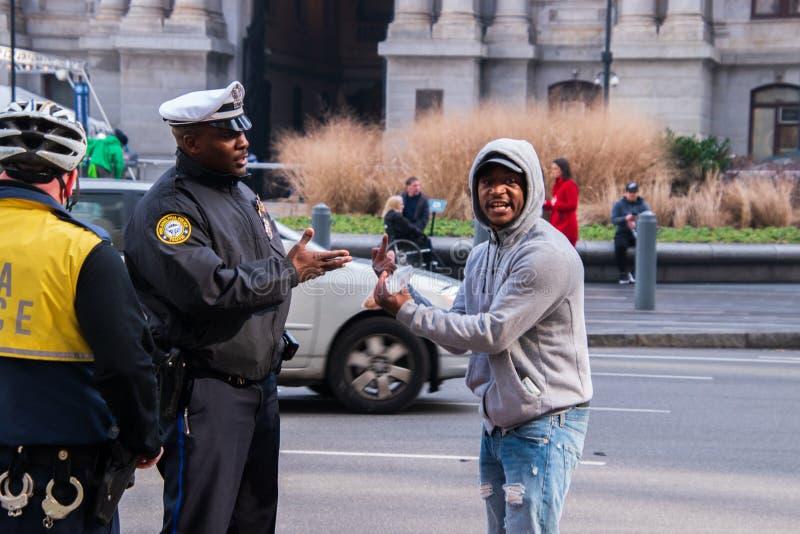 Svart man som gör obscen gest till en Philadelphia polis royaltyfri foto
