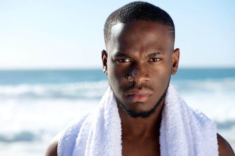 Svart man som poserar med den vita handduken på stranden royaltyfri bild