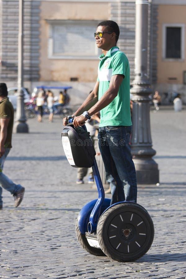 Svart man som rider blått segway arkivfoton