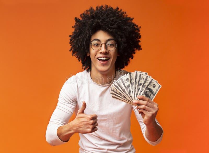 Svart man som rymmer pengar på orange bakgrund royaltyfri foto