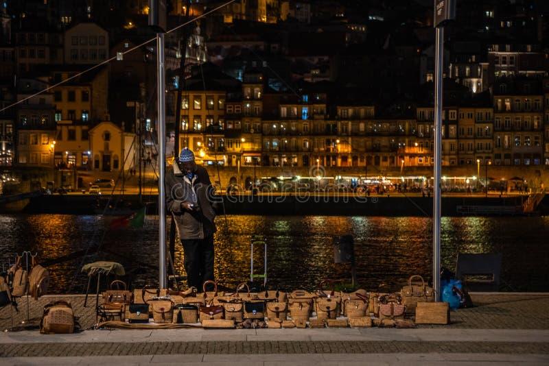 Svart man som säljer material i gatan under en kall natt av winterjpg royaltyfria foton