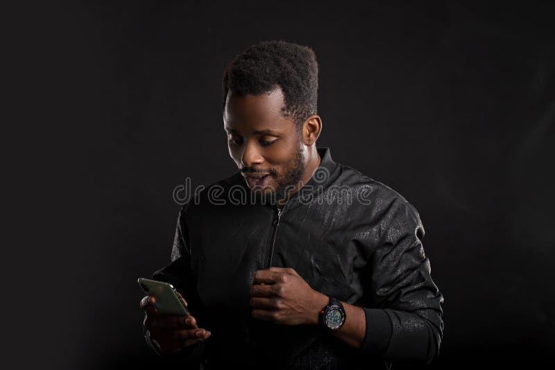 Svart maninnehavmobiltelefon i m?rker royaltyfri foto