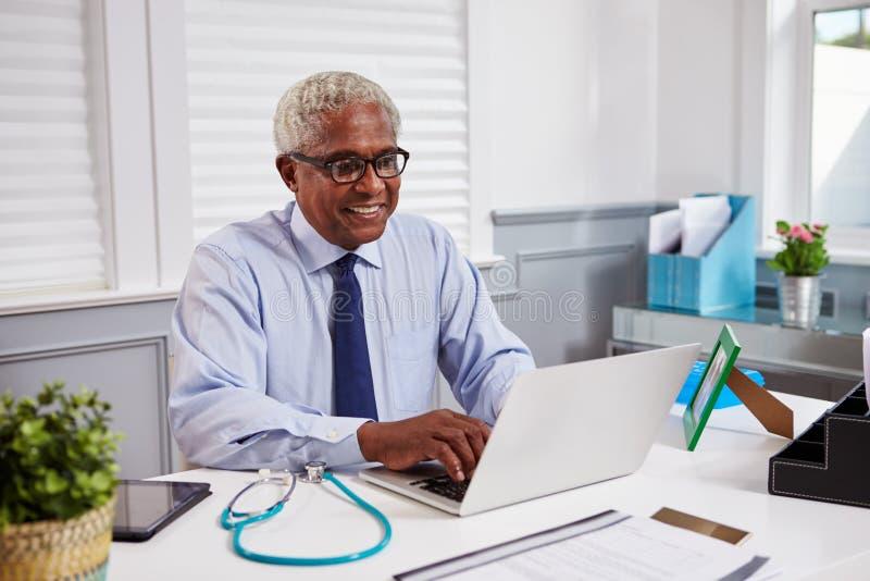 Svart manlig doktor för pensionär på arbete genom att använda bärbara datorn i ett kontor royaltyfri foto