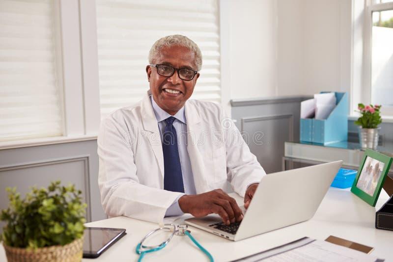Svart manlig doktor för pensionär på ett kontorsskrivbord som ser till kameran royaltyfri bild