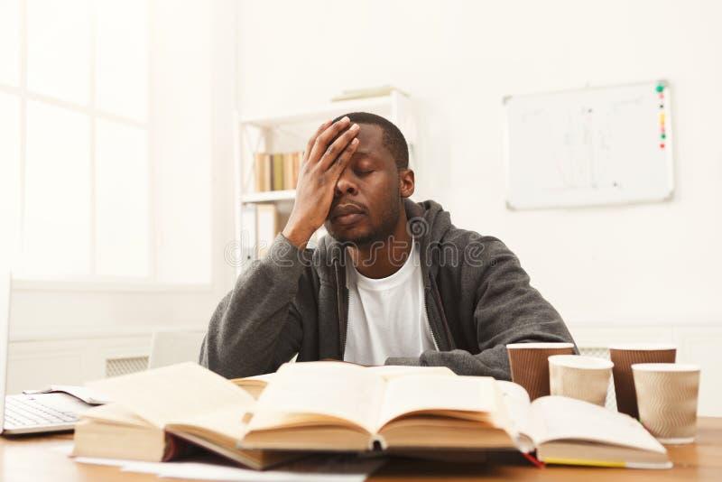 Svart manlig student som mycket studerar på tabellen av böcker royaltyfri bild
