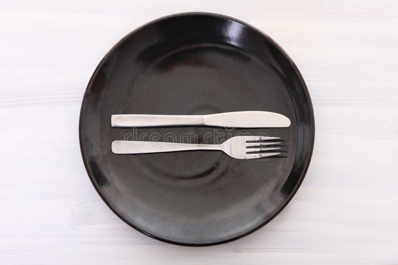 Svart maträtt på den vita trätabellen med den UTMÄRKTA bestickbetydelsen fotografering för bildbyråer