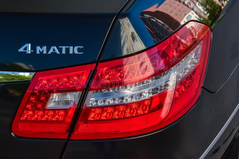 Svart Mercedes Benz E-grupp E350 2011 ?r bakre taillampsikt med m?rkt - gr? inre i utm?rkt villkor i en parkeringsplats royaltyfri bild