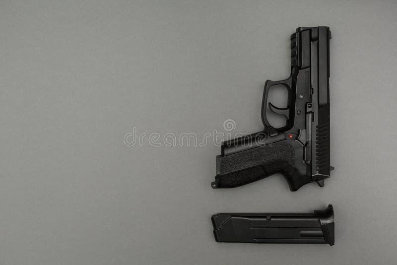 Svart metall 9mm pistol och tidskrift på grå bakgrund royaltyfria bilder