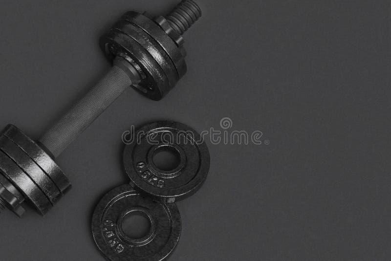 Svart metallhantel för kondition på grå bakgrund arkivfoto