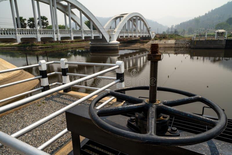 Svart metallkugghjul som kontrollerar dammluckan med texter i betydelse för thailändskt språk 'egenskapen av 'och sikten av vitt  arkivfoton