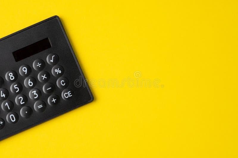 Svart minsta räknemaskin på fast gul bakgrund med kopieringsutrymme genom att använda för finansiell aktivitet, redovisning, skat arkivfoto