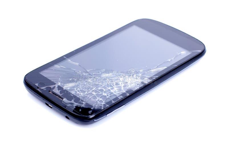 Svart mobiltelefon med en bruten skärm på en isolerad backgroun arkivfoto