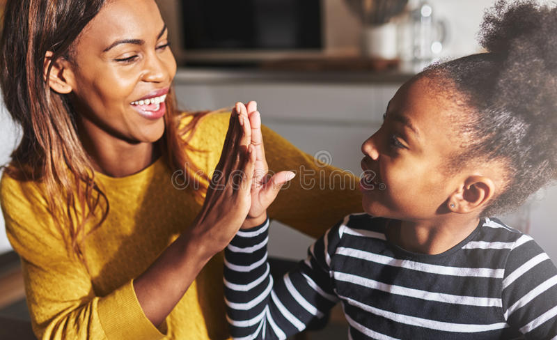 Svart moder och barn höga fem arkivbild