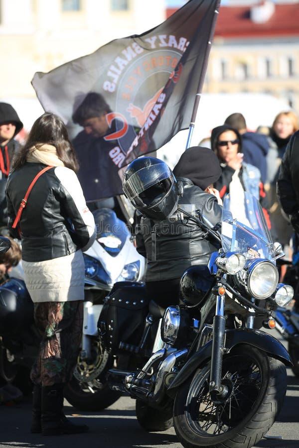 Svart motorcykel med en genomskinlig flagga och folk runt om den arkivbilder