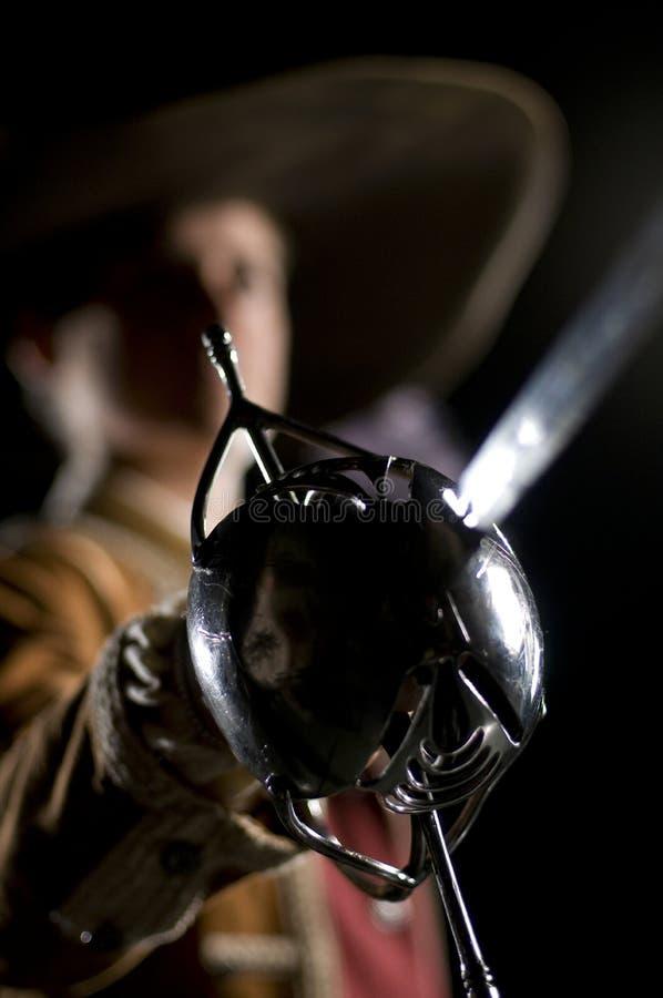 svart musketeer o för bakgrund över swordsman arkivbilder