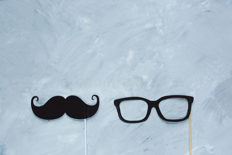 Svart mustasch, exponeringsglas från papper på pinnen på den gråa grungebakgrunden royaltyfri foto