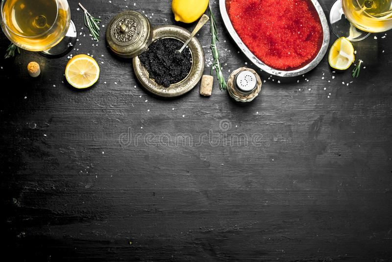 Svart och röd kaviar med citronskivor arkivfoto