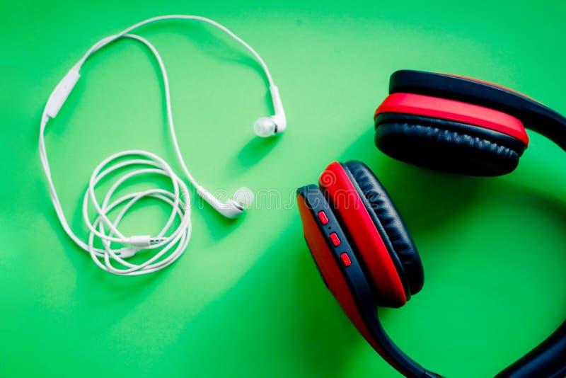 Svart och röd läder för trådlöst Över-öra i naturlig storlek hörlurar som, isoleras på grön bakgrund med urklippbanan Uppsättning fotografering för bildbyråer