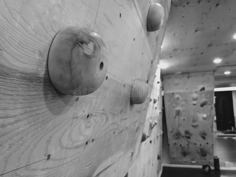 Svart och vit stängning av klätterväggen för simulering av klättring i ett gym för att passa och träna som förberedelse för royaltyfria foton