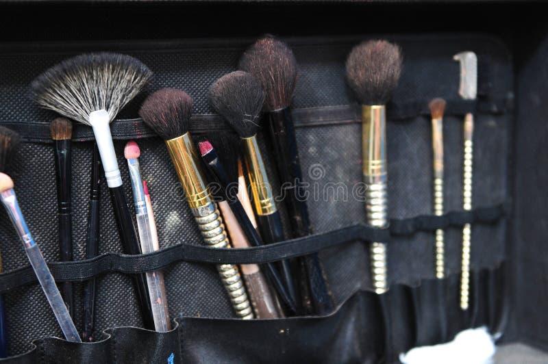 Svart påse med makeupborstar arkivbild
