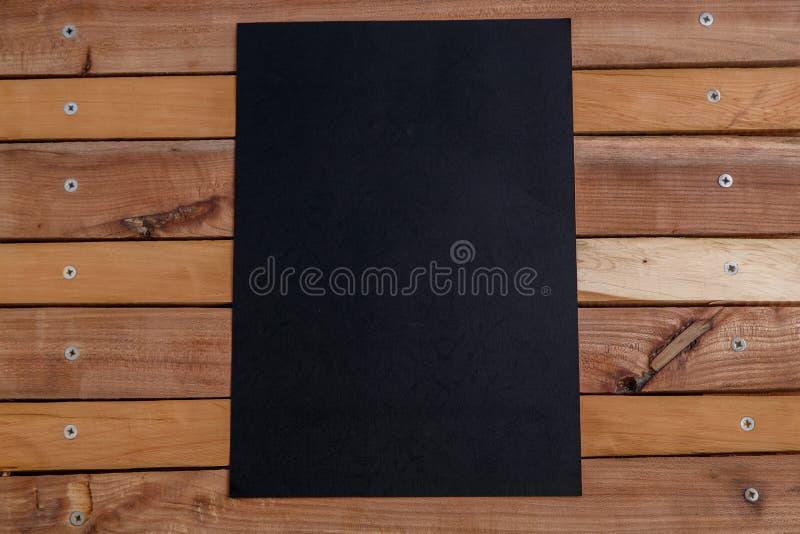 Svart papper på en naturlig träbakgrund ovanför sikt arkivbild