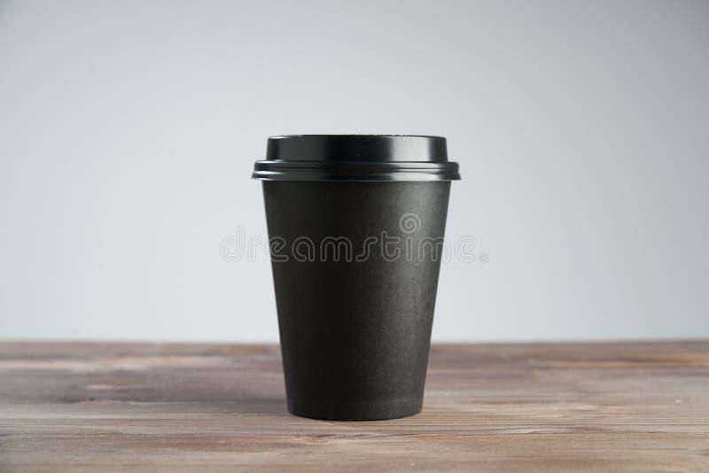 Svart pappers- kaffekopp som är disponibel för tagande bort eller att gå, på trätabellen, utrymme för designorientering arkivfoton