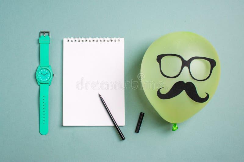Svart pappers- mustasch och exponeringsglas på ballongen och en notepad med en tuschpenna fotografering för bildbyråer