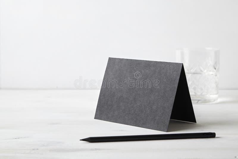 Svart pappers- vykort och blyertspenna på trätabellen brevpapper Tomt utrymme för designorientering royaltyfri foto