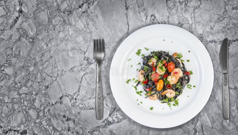 Svart pasta för tioarmad bläckfiskfärgpulverFettuccine med räkor eller körsbärsröda tomater för räkor, persilja, chili i vin och  royaltyfria bilder