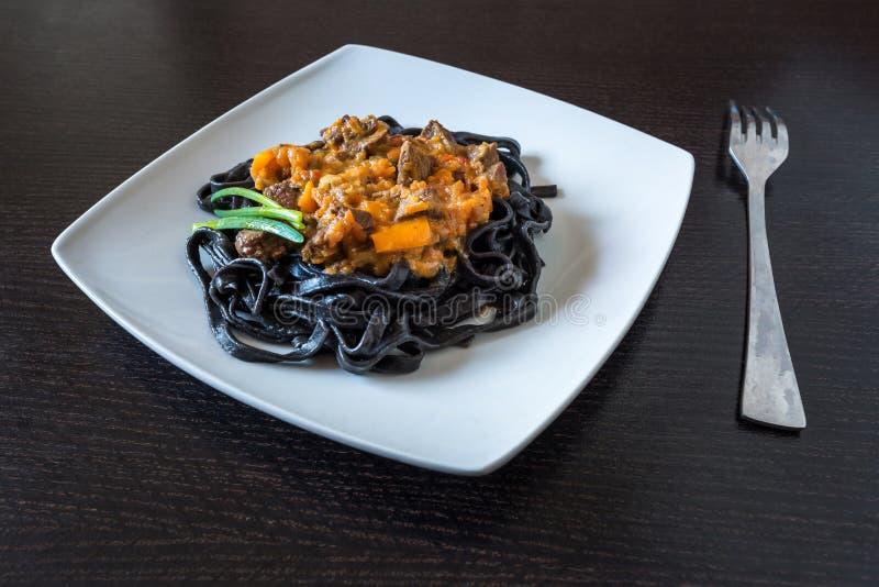 Svart pasta med bläckfiskfärgpulver Pasta av mannagryn för durumvete med tioarmad bläckfiskfärgpulver med sås för nötköt royaltyfria bilder