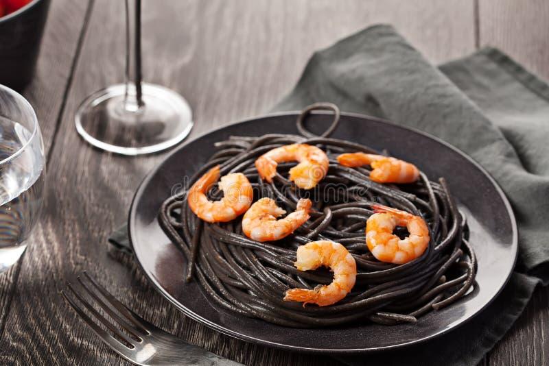 Svart pasta med räkamat på mörk bakgrund fotografering för bildbyråer