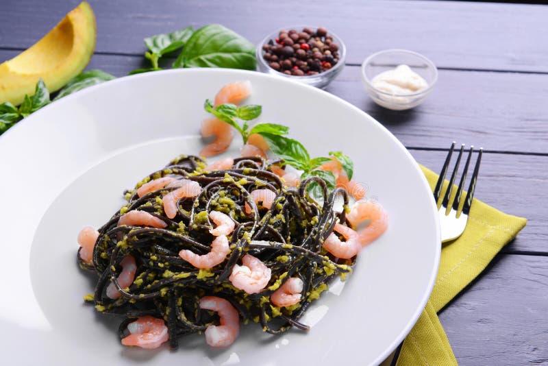 Svart pasta med räkor och avokadosås på plattan royaltyfri bild