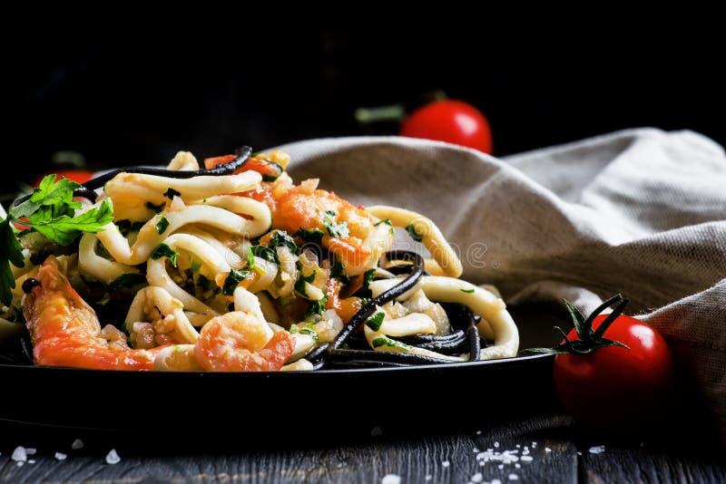 Svart pasta med skaldjur- och tomatsås på en platta, svärtar tillbaka fotografering för bildbyråer