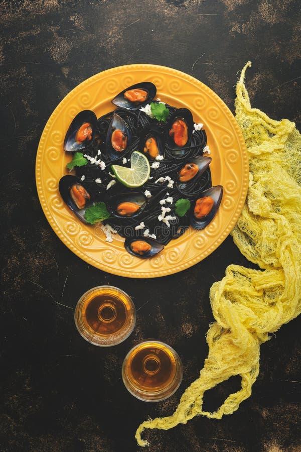 Svart pastaspagetti med havs- musslor på en gul platta med vitt vin, textiler, mörk lantlig bakgrund Bästa sikt, lekmanna- lägenh fotografering för bildbyråer