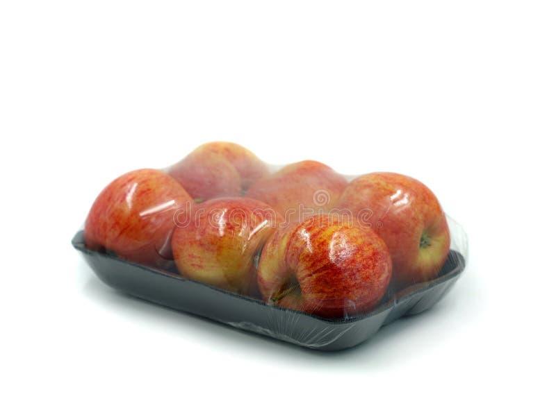 Svart peel med sex äpplen som slås in i genomskinlig plast- som isoleras på vit bakgrund arkivfoton