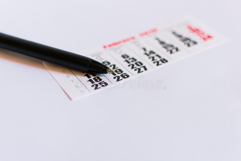 Svart penna på en tom kalender på vit bakgrund arkivfoton