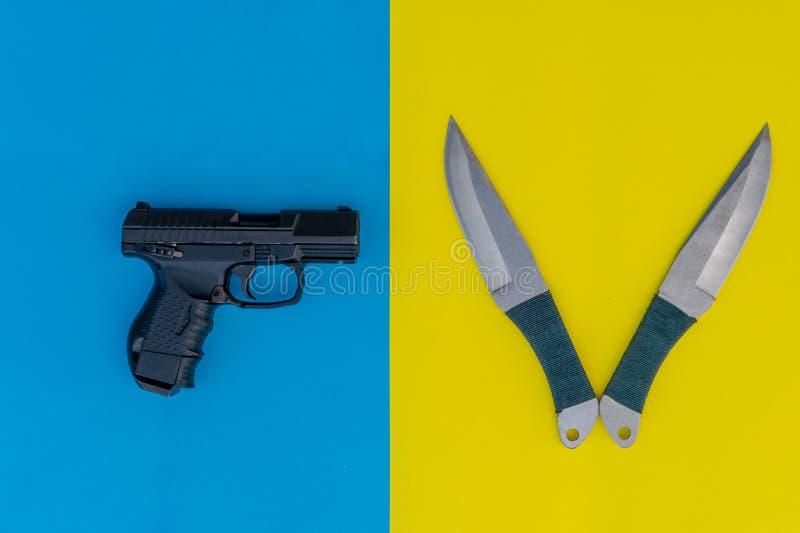 Svart pistol och två kasta knivar på en kulör bakgrund bl? yellow f?r bakgrund arkivbild