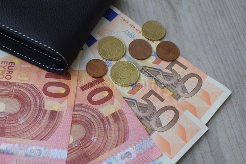 Svart plånbok med eurovalutasedlar och mynt arkivbilder