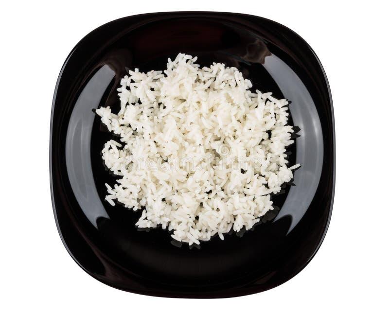 Svart platta med kokta vita ris som isoleras på vit arkivfoto