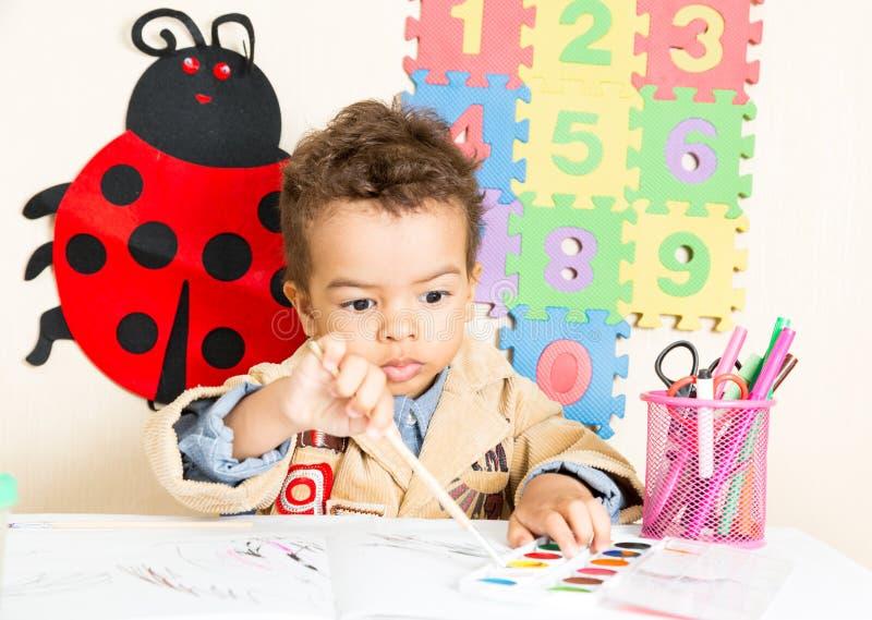 Svart pojketeckning för afrikansk amerikan med färgrika blyertspennor i förträning a i dagis royaltyfri foto