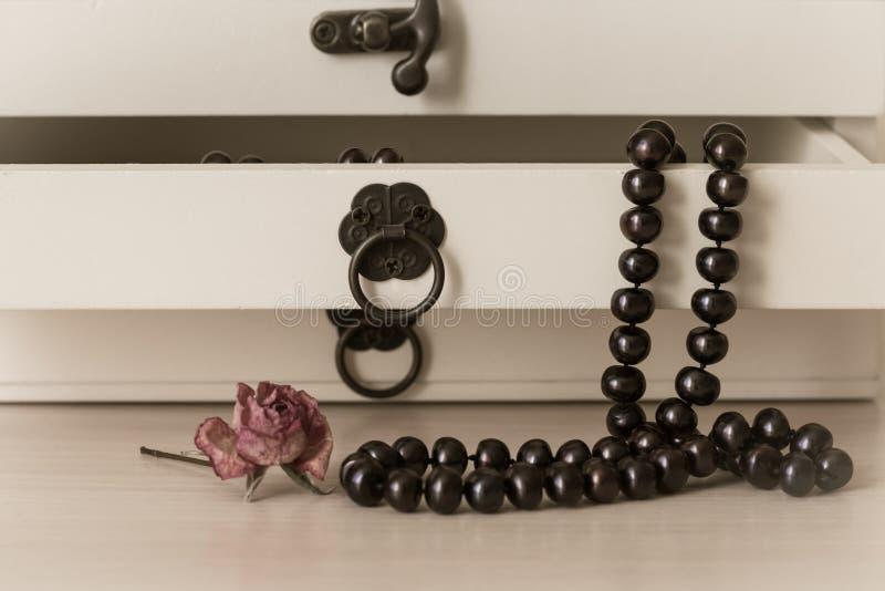 Svart pryder med pärlor halsbandet i en träcasket arkivbilder