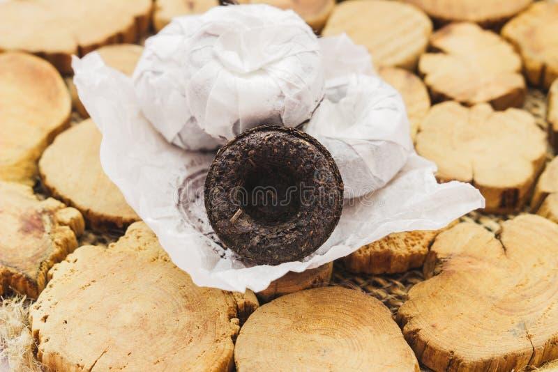 Svart Puer te på en träställning arkivfoto