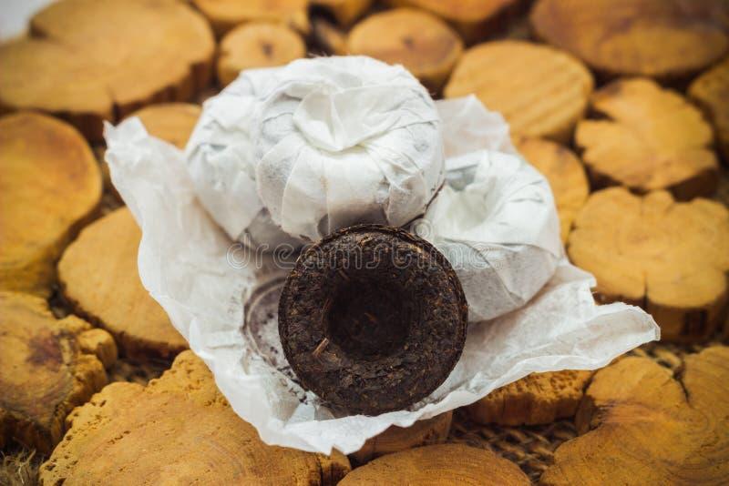 Svart Puer te på en träställning arkivfoton