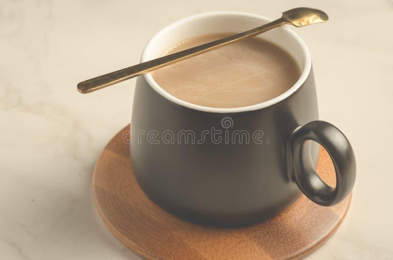 svart rånar av en cappuccino med en sked i en träservice, på en vit tabell royaltyfri fotografi