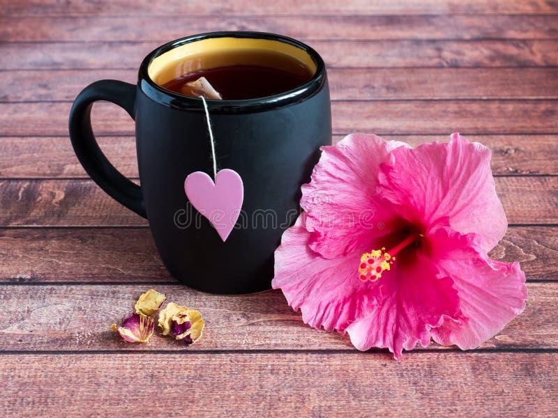 Svart rånar av te med en rosa hjärta på en rosa hibiskusblomma för rad på mörk wood bakgrund arkivfoto